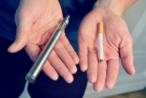 man holding electronic cigarettes and cigarettes